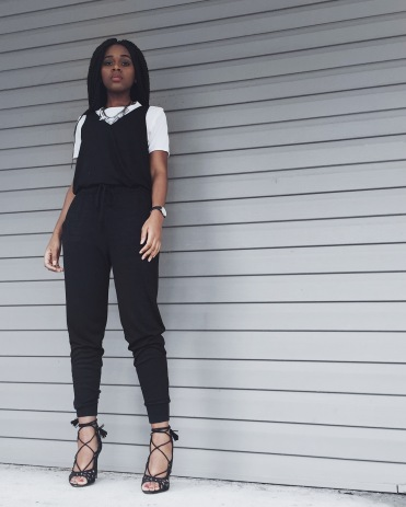 white t-shirt, black jumpsuit, diamond necklace, black watch, black lace up heels